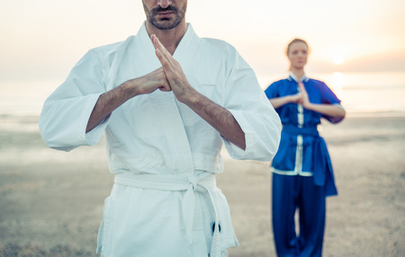 Martial-Arts-Grüße. Paar-Training auf dem Strand am Morgen