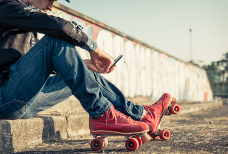 adult 80s: Young skater boy with smart phone sitting and taking a break Stock Photo