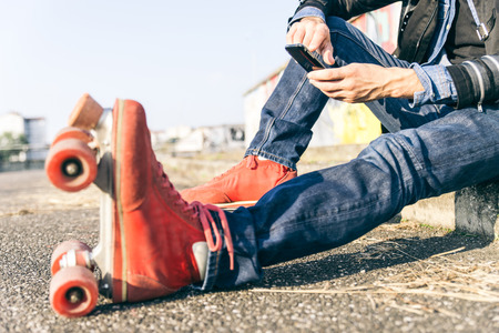 80s adult: Young skater boy with smart phone sitting and taking a break Stock Photo
