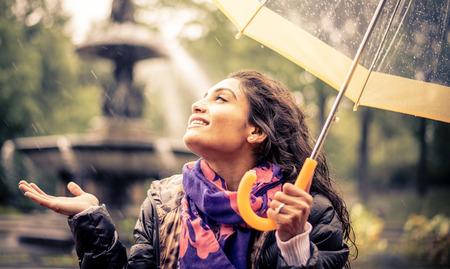 Счастливая женщина под дождем улыбается держа зонтик Фото со стока