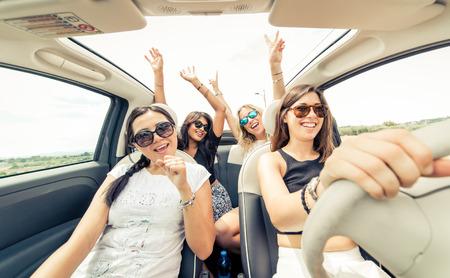 Grupo de chicas divirtiéndose con el coche. Tomar selfie mientras conduces