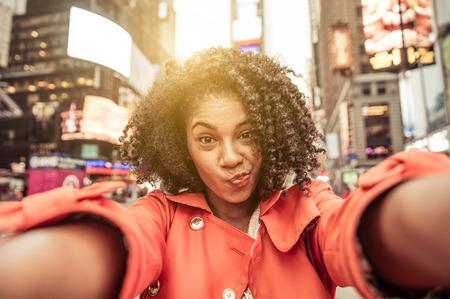mujeres africanas: Joven mujer de raza toma autofoto en Nueva York, Times Square