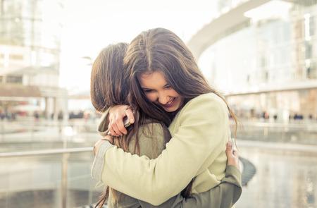 Две девушки обнимали друг друга после того, как долго они были на расстоянии Фото со стока