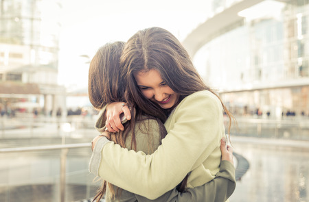 personas abrazadas: Dos muchachas que abrazan unos a otros después de mucho tiempo han sido distante