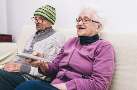 home health care: old couple watching television. man and woman sitting on the couch and making tv zapping