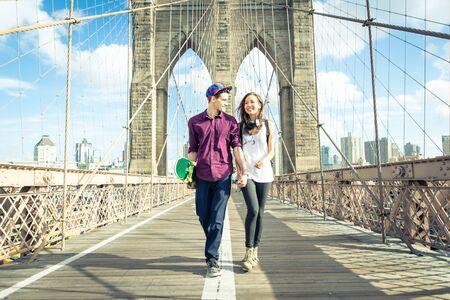 ブルックリン橋の上を歩く若いカップル 写真素材
