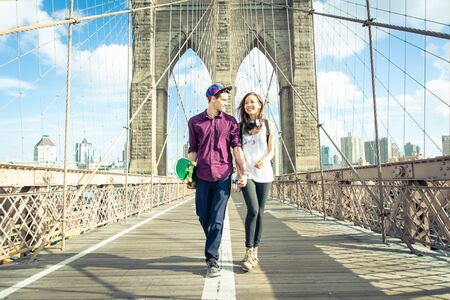 Young couple walking on the brooklyn bridge Stock Photo