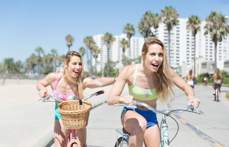 venice: Twin sisters going on the bicycle in Venice beach Stock Photo