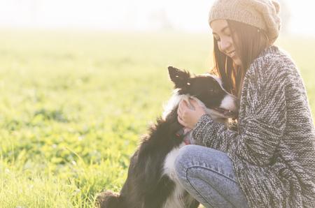 động vật: phụ nữ trẻ chơi với con chó collie biên giới của mình. khái niệm nghị đến động vật và con người