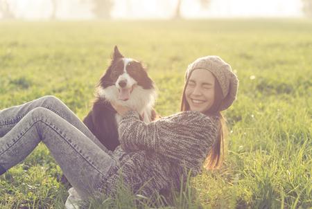 그녀의 보더 콜리 강아지와 함께 연주 젊은 여자. 동물과 사람 AOUT 개념 스톡 콘텐츠