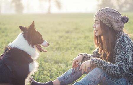 mujer con perro: Mujer joven que juega con su perro border collie. concepto aout animales y personas Foto de archivo