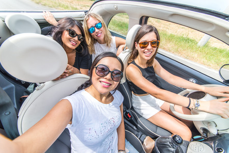airiness: Group of girls having fun with the car. Taking selfie hile driving