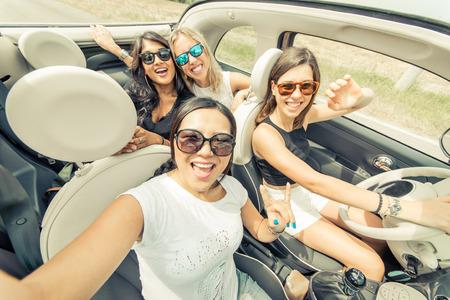 canto: Grupo de muchachas que se divierten con el coche. Tomando selfie conducci�n hile Foto de archivo