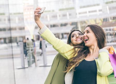 belle brunette: Deux belles filles faisant du shopping dans le centre-ville et prendre un selfie avec un t�l�phone intelligent