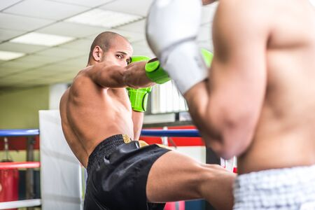 thai arts: Fighters fighting on the ring. Kickboxing match in the gym.Concept about training and fighting Stock Photo