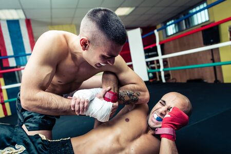 grappling: Fighter makes submission and arm lock at the ground