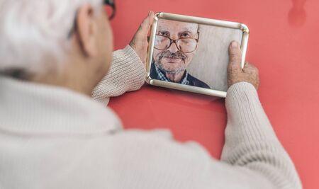Oude vrouw op zoek naar haar man foto.