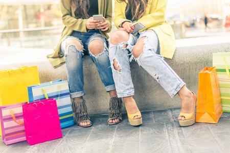 comprando zapatos: Dos muchachas que se sientan en un centro comercial y mirando a los teléfonos inteligentes Foto de archivo