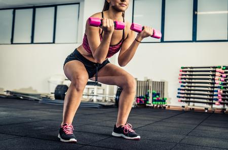 en cuclillas: Mujer joven atlético hacer ejercicios en cuclillas para las nalgas Foto de archivo