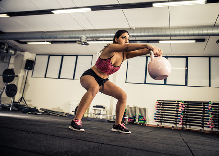 female ass: Athletic young woman doing squat exercises for the buttocks Stock Photo