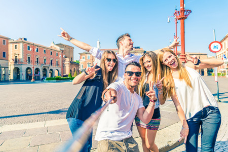 people street: Group of happy friends taking a selfie with stick outdoors