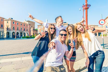 Grupo de amigos felices de tomar un selfie con palo al aire libre