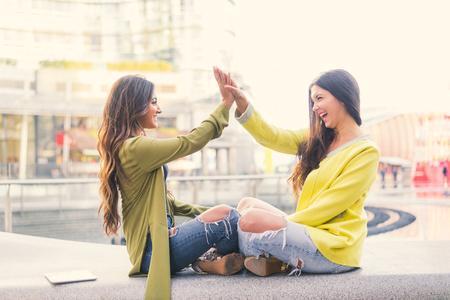 secret love: Two beautiful young women giving high five Stock Photo