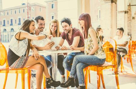 persona sentada: Grupo de estudiantes que se sientan en un café bar mirando tableta - amigos alegres jovenes que se divierten con la computadora portátil - Las personas activas viendo una película divertida en línea