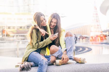 jeune fille: Amis euphoriques regarder des vid�os sur un smartphone et de pointage � l'�cran surpris Banque d'images
