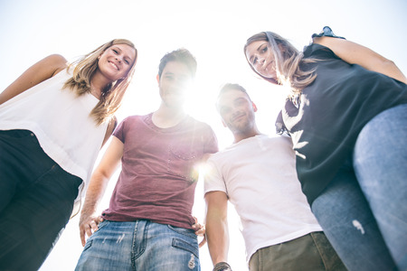 good looks: Four young people looking down at camera with backlight and sunflare Stock Photo