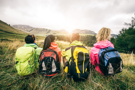 Four backpackers looking at sunset over the mountains