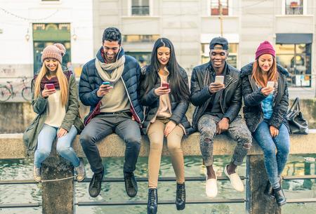 persona sentada: grupo multicultural de amigos utilizando tel�fonos celulares sentado en una fila Foto de archivo