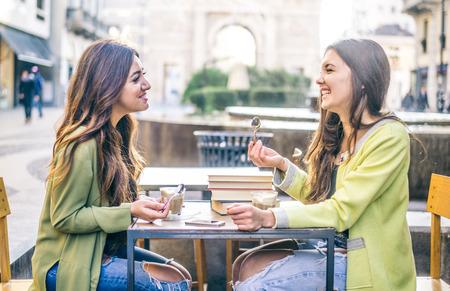 Duas amigas bonitas rindo enquanto está sentado em um bar ao ar livre