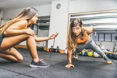 strength training: Sportive woman making pushups with one hand - Athlete training in a gym with coach - Girls working out in a fitness center