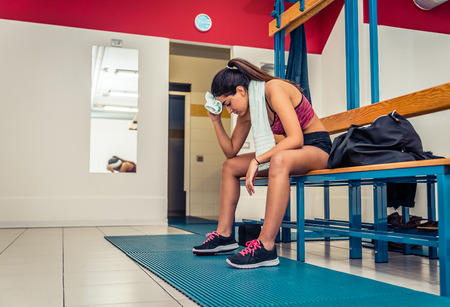 gym room: Athletic woman relaxing in a gym locker room after an intensive workout