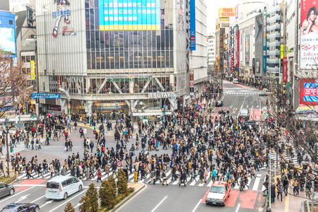 scramble: TOKYO, JAPAN - FEBRUARY 7, 2015: Pedestrians crossing Shibuya Square.The crossing is one of the worlds most well known examples of a scramble crosswalk