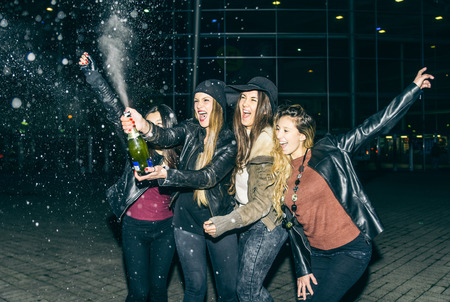Women opening and sprinkling a white wine bottle