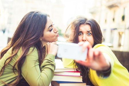 Two girlfriends taking a selfie in a bar outdoors Stock Photo