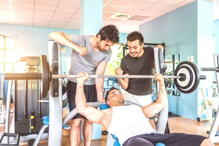 buddies: Three friends working out in a weights room