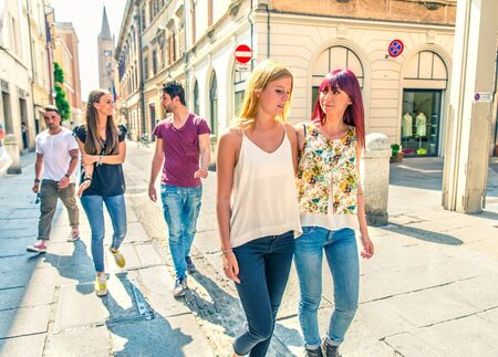 students group: Group of friends walking outdoors while speaking and gesturing