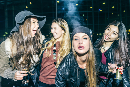 drugs: Group of four pretty girls having party, smoking and drinking alcohol Stock Photo