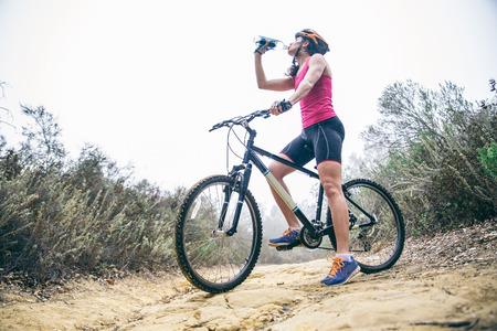 ciclo del agua: Deportiva mujer de agua potable, mientras que en una bicicleta de entrenamiento