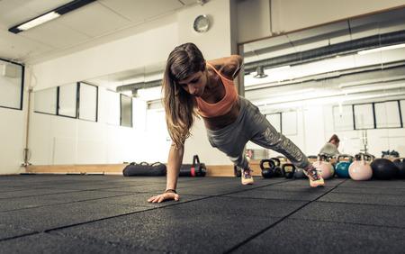 actitud: Mujer haciendo flexiones en una mano. Concepto sobre el deporte, fitness y bienestar