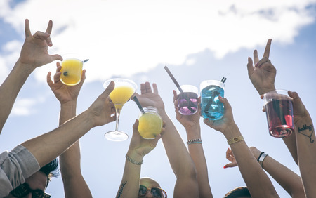 fruit bars: People making party and dancing on a beach party. Holding cocktails and pointing to the sky.