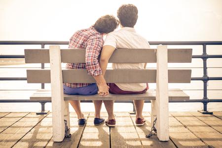 sex: gelukkig paar in liefde in Santa Monica zittend op een bankje. Mensen en relatie-concept