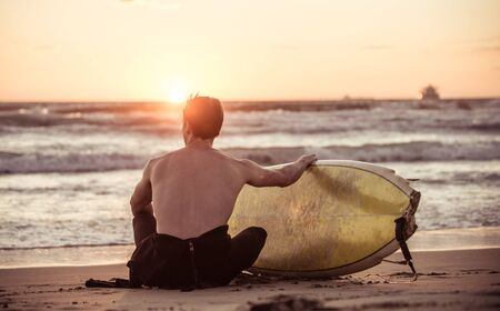 surf: Surfer taking a break on the beach. Concept about sport, wellness and people