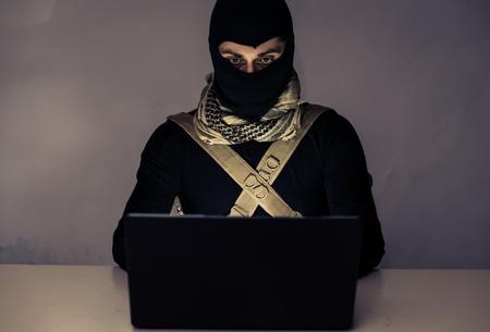 Террорист, работающий на своем компьютере. Понятие о международном кризиса, войны и терроризма Фото со стока