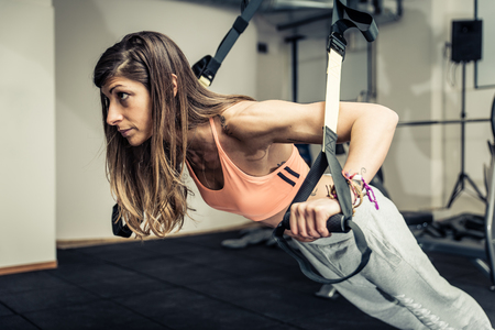 pectoral: Woman training with elastics in the gym. Concept about Fitness and sport Stock Photo