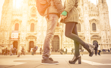 young woman legs up: Couple kissing in Duomo square, Milan. Pavement and floor view with focus on the couple shoes.