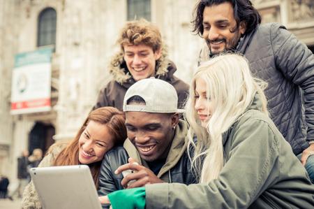 Gruppo di amici a guardare video divertenti su una tavoletta digitale. Amici di etnia diversa nel centro di Milano